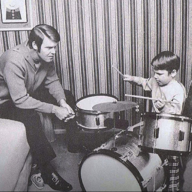 Travis with his dad and his first set of drums