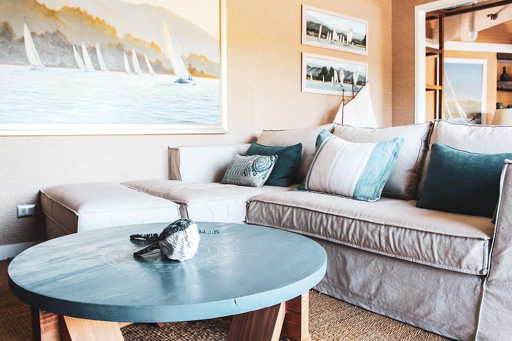 Una sala de estar para reunir a la familia, Colores neutros y toques de azul en cojines y cuadros. La rafia en el muro aporta gran calidéz. Se hizo un mueble mural medida, de carácter rústico, con trozos de madera natural en sus puertas.