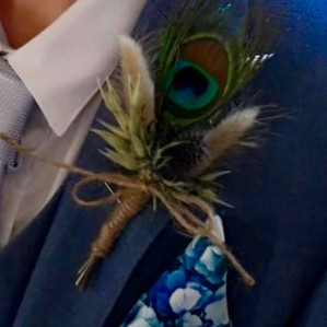 Peacock feather and dried flower buttonh