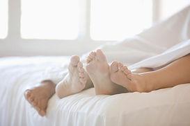 Pies del par en la cama