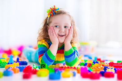 Little girl in a bright shirt laying in a pile of PCIT Toys (Legos) with her hands on her cheeks