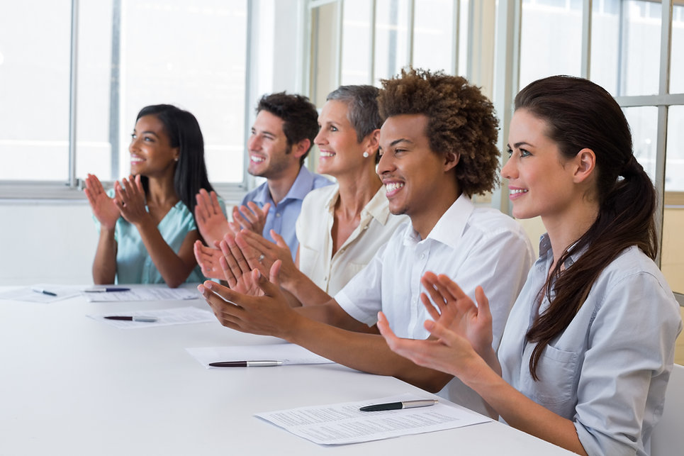 5 adults in a training who are smiling and clapping.  This is to represent the Certified PCIT Site Trainer format