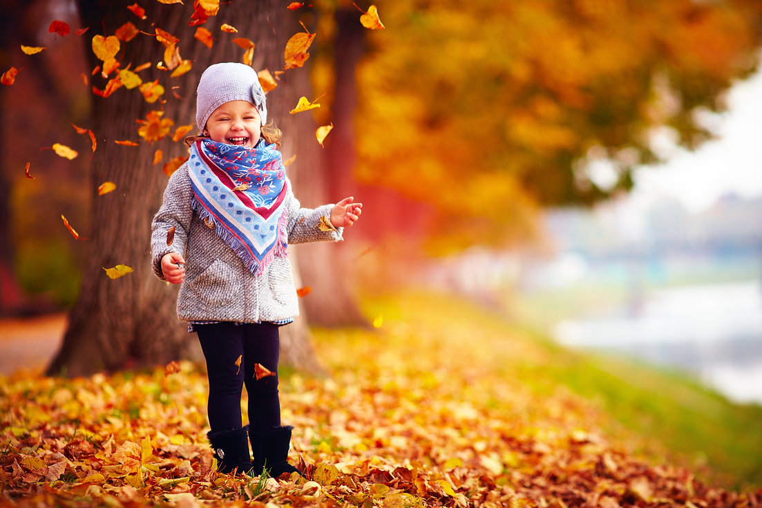 Girl smiling with leaves falling behind her to symbolize falling prices for PCIT Training