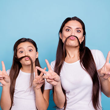 Girl and her mother showing peace signs to represent Step 2 of PCIT Certification Training