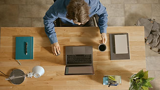 Guy sitting in front of his laptop drinking coffee to highlight the PCIT Online Training Experience.jpg