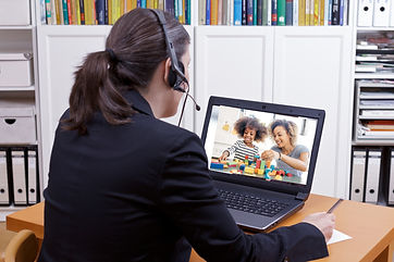 Woman with a headset providing iPCIT (telehealth PCIT) to a mother and daughter through her laptop.