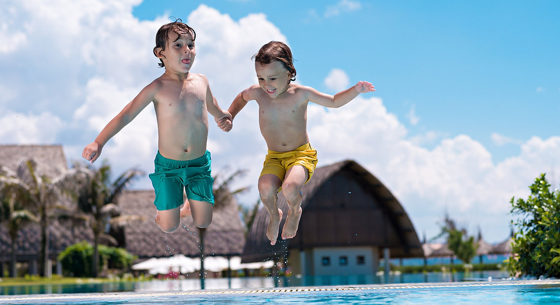 Two boys smiling and jumping into a pool to symbolize jumping into PCIT Training