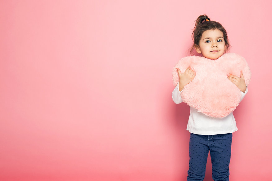 Young girl holding a pink heart pillow to show thanks for contacting the PCIT Training program