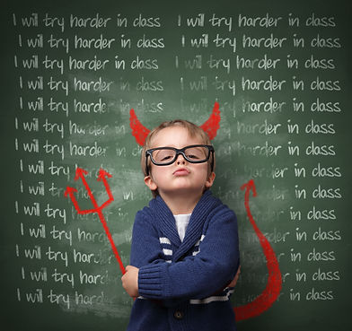 Cute boy in glasses dressed a the devil in front of a chalkboard to symbolize behavioral challenges in TCIT classrooms