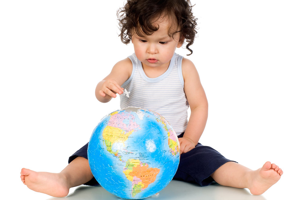 Small boy putting a puzzle piece into a 3-dimensional world globe. The picture has the 12 International countries where PCIT research has been conducted.