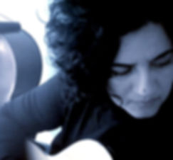 Blue tinted close up photo of Lourdes Perez with black curly hair looking down playing an acoustic guitar with a cello partially shown behind her.