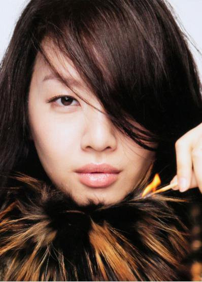 Asian model holding lit match while wearing flammable fur