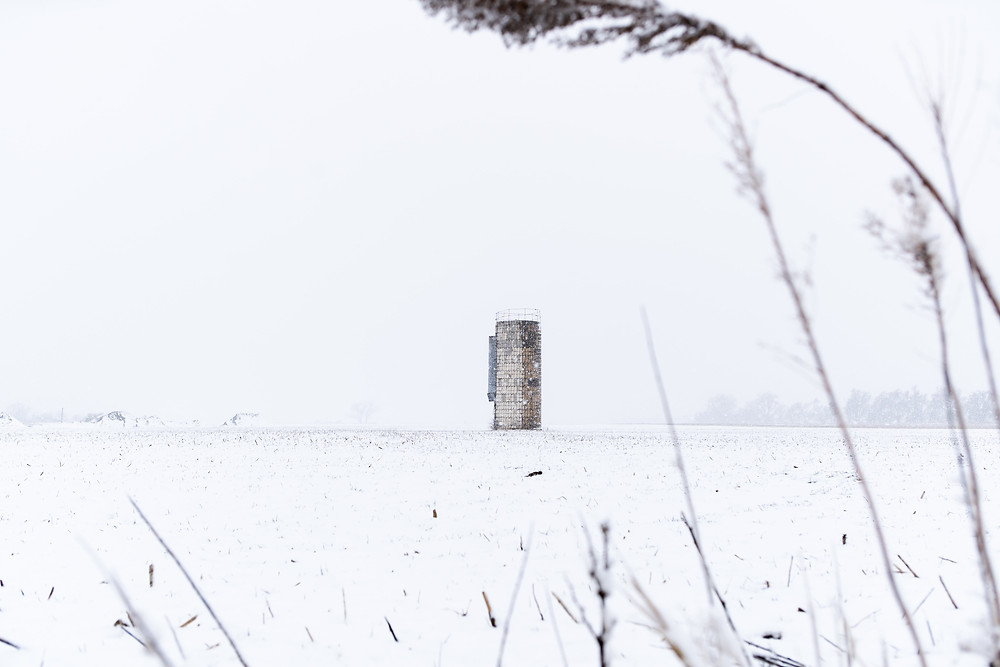 Sad little silo by itself in the middle of a snow-covered field