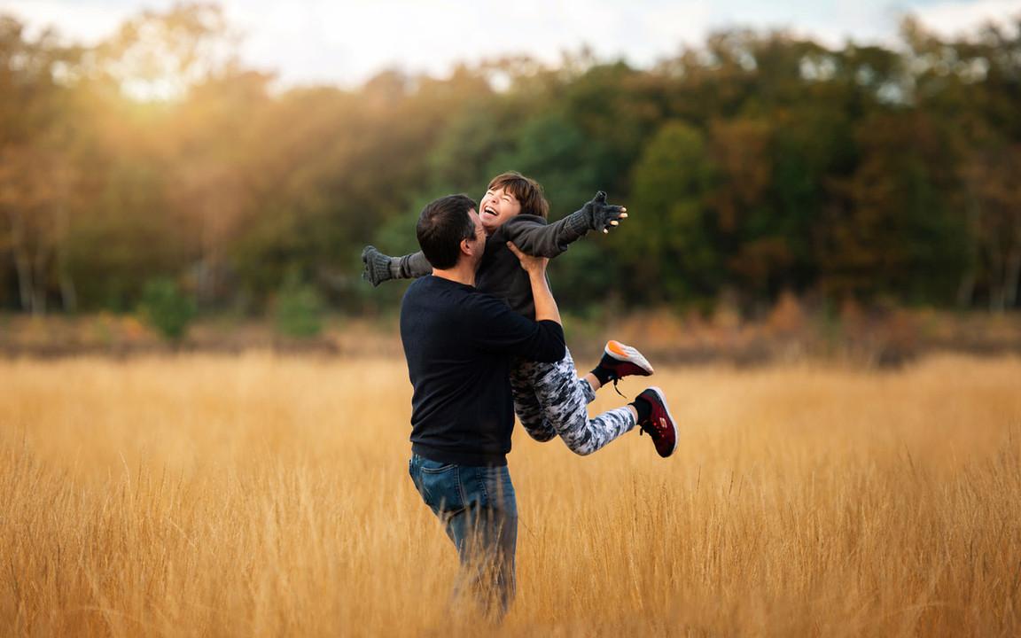 father-daughter-jump-golden-field.jpg