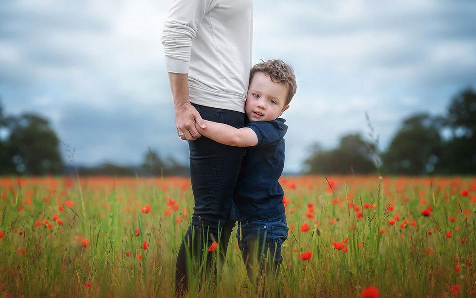boy-holding-mothers-legs-poppy-field-surrey.jpg