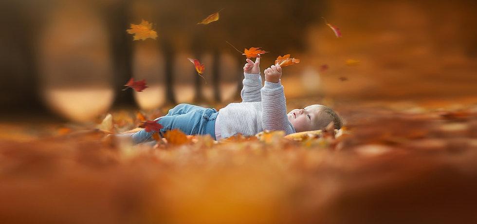 Surrey-baby-photographer-captures-baby-catching-autumn-leaf