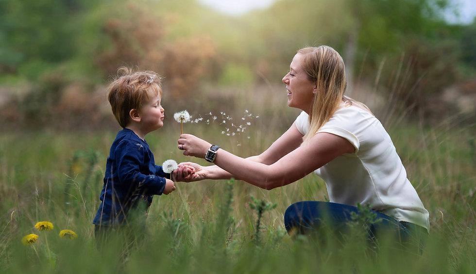 surrey-portrait-photographer-captures-toddler-blowing-dandelion.jpg