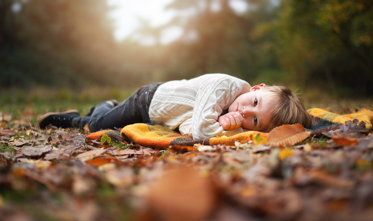 boy-laying-autumn-leaves.jpg
