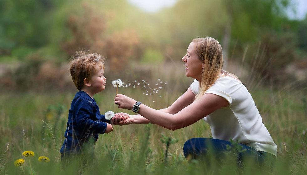 boy-blowing-dandelion-holding-mothers-hand-field.jpg