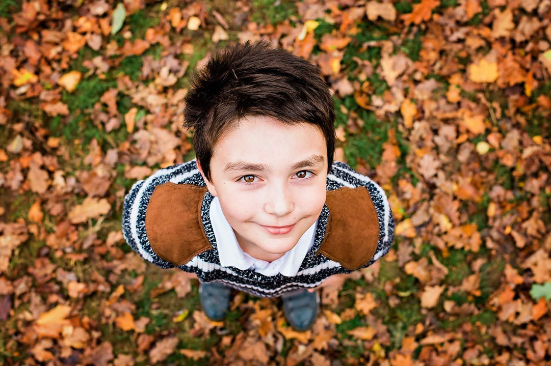 boy-looking-up-at-camera-autumn-leaves.jpg