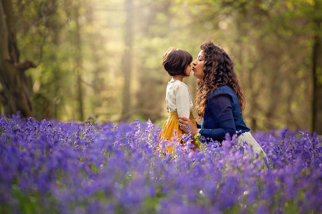 mother-kisses-daughter-in-bluebells.jpg
