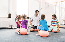 A teacher and four elementary-age students sit on large bouncy balls in a circle.