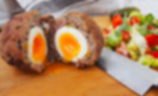 Traditional _Scotch egg_ on a wooden pla