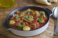 Pork, chorizo and pea stew topped with b