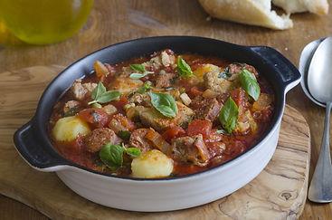 Pork, chorizo and pea stew topped with b