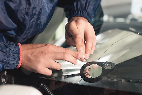 close up of technitian repairing a windshield chip.