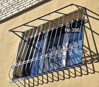Дугообразная сварная металлическая решетка на окно с козырьком.
