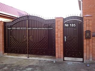 Металлические ворота с калиткой рядом коричневого цвета с ковкой