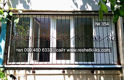 Прямая металлическая решетка на окно с коваными элементами.