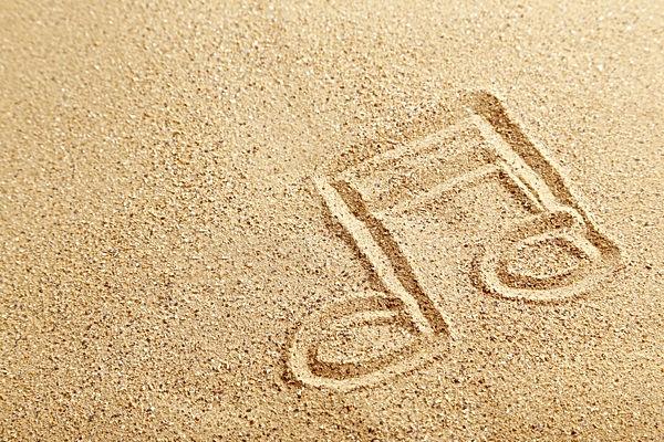 Music note drawn on a beach sand.jpg