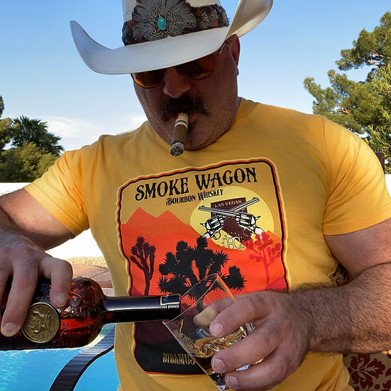 Smoke Wagon logo overlapping a sun, behind a mountain range and Joshua tree forest on a yellow tee worn by Aaron