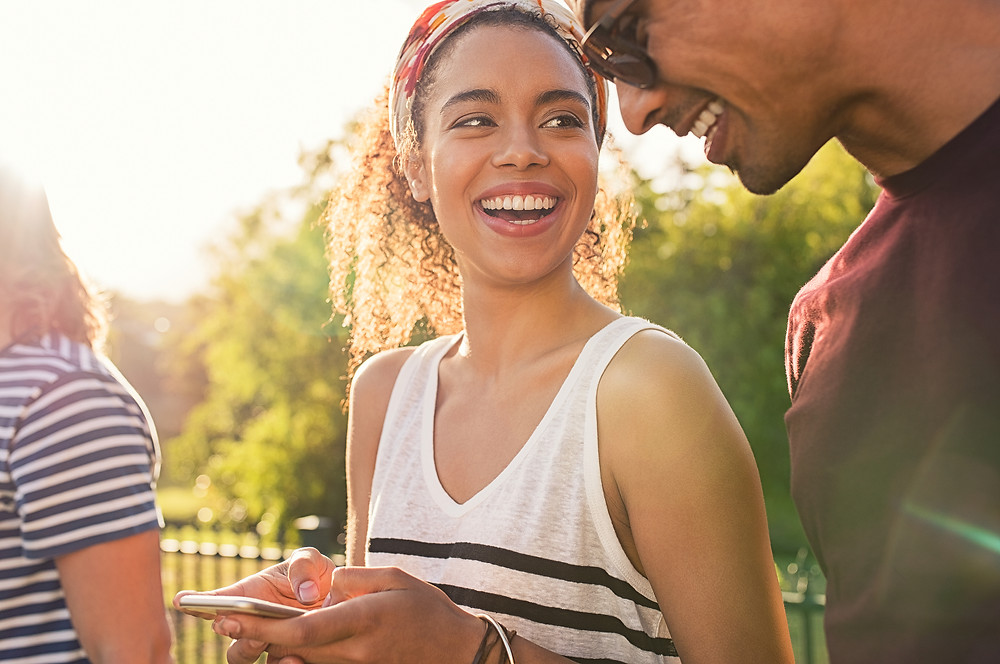 black couple smiling keeping a food record on phone