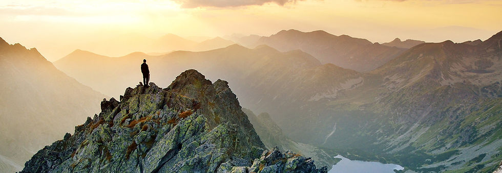 Man standing on mountain top looking off into the distance