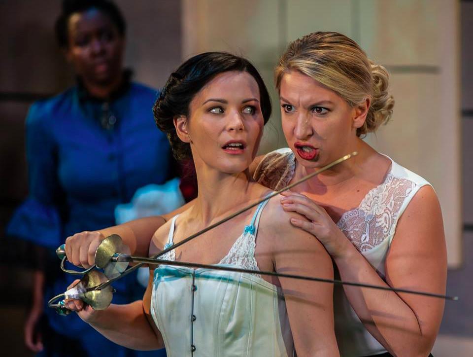 Susan Swayne (Lisa DeRoberts) locks swords with Katherine Denn (Jordan Trovillion) while Isabelle Fontaine-Kite (Ernaisja Curry) looks on.
