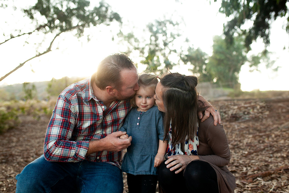 Family kissing daughter during a family photoshoot