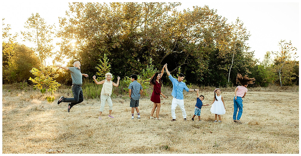 Extended family jumping at family session