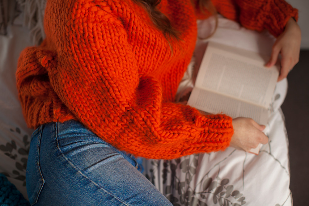 Kate wearing a bright orange knit and reading a book