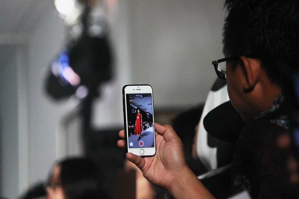 Man filming a catwalk show on his smart phone