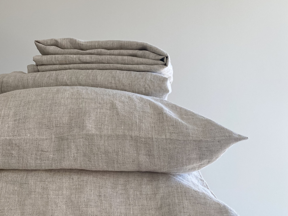 Pile of cushions and folded hemp sheets in a natural beige colour