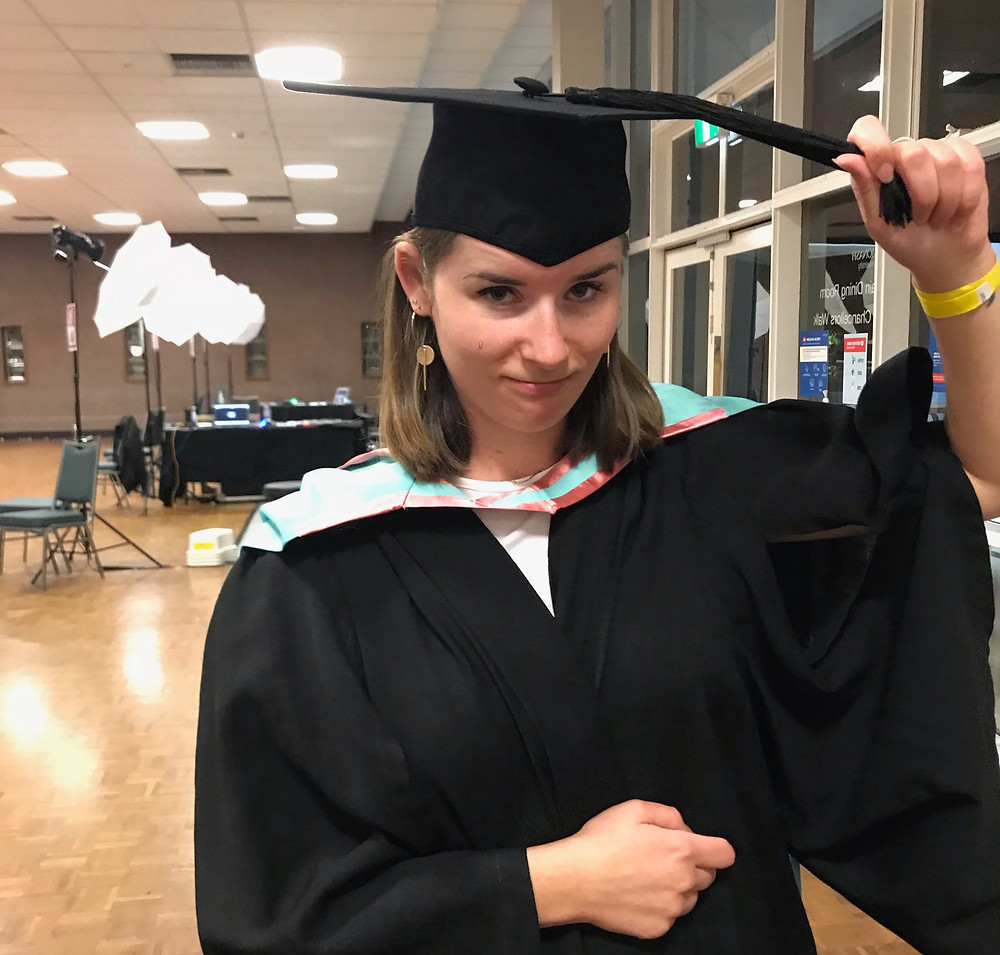 Kate dressed in academic robe and hat when graduating
