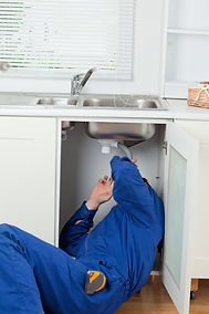 Portrait of a plumber fixing a sink in a