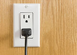 Electrical outlet with black power cord.