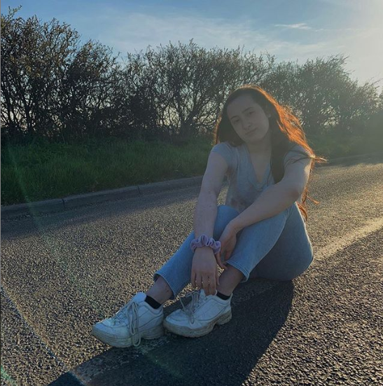 Girl sitting on a road in the sun
