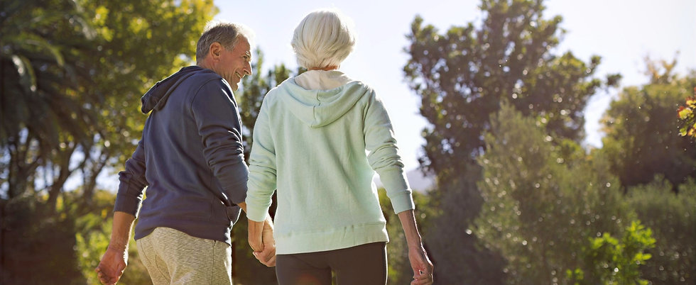 Older man and woman walking walking in park holding hands