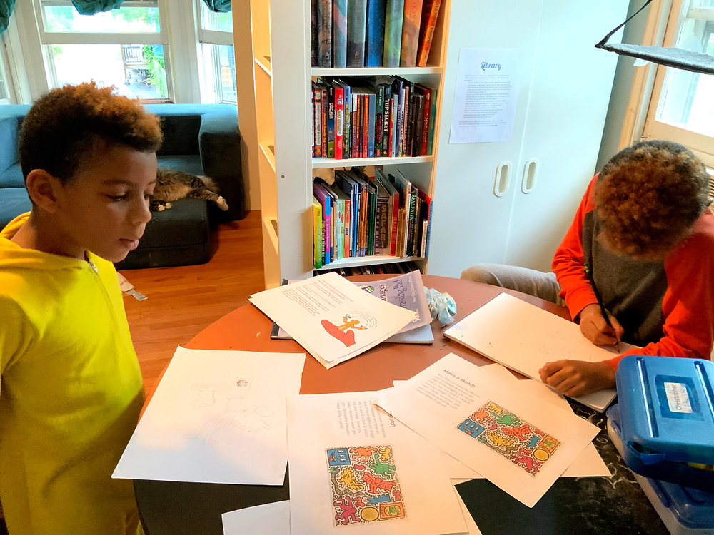 Juju and Blaze draw with scattered reference images of Keith Haring's work between them.