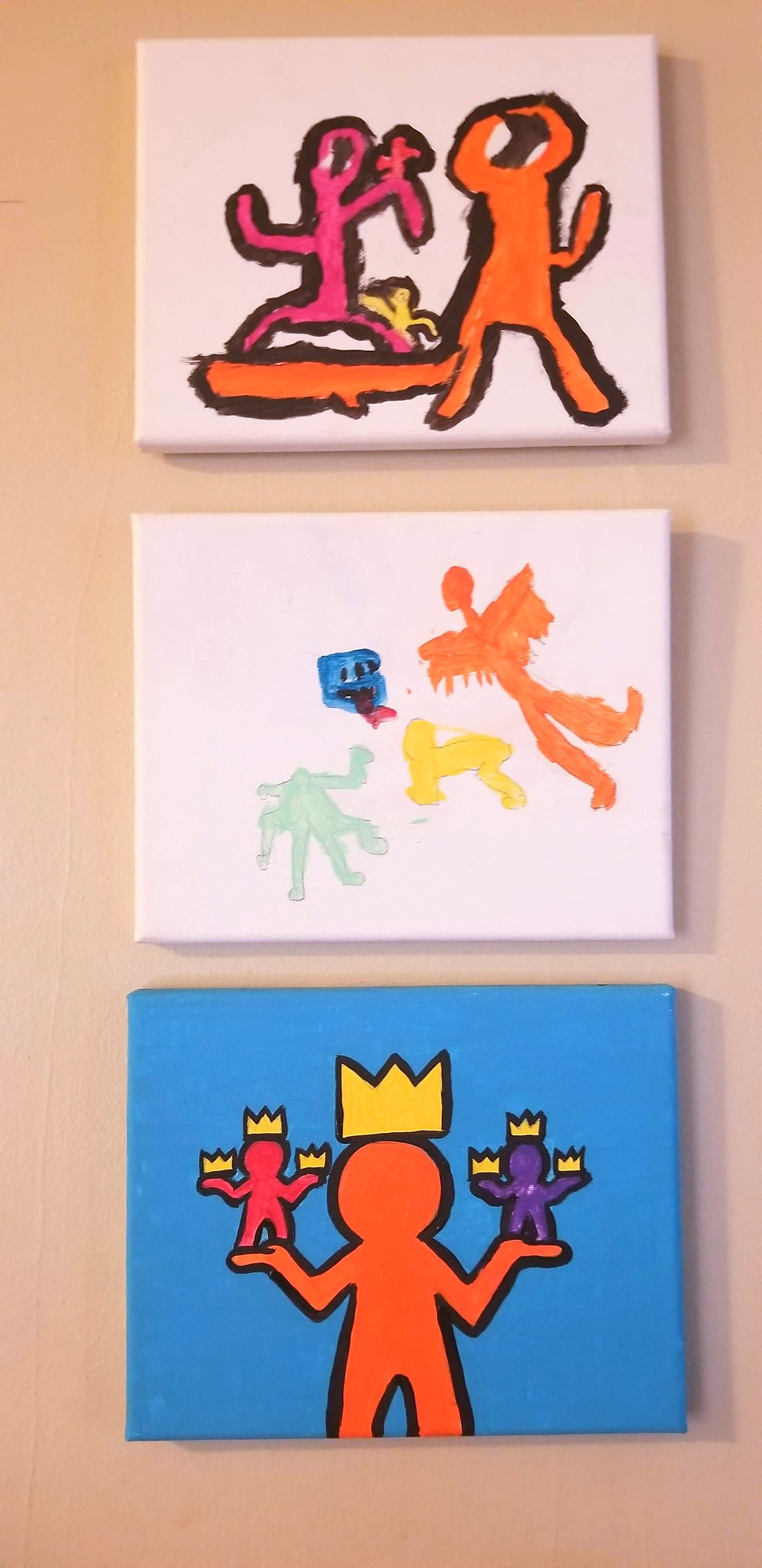 Three paintings inspired by Keith Haring hanging on the wall.